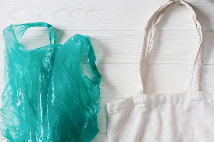 ban plastic. plastic bag with eco natural reusable tote bag for shopping, flat lay on rustic background. sustainable lifestyle concept. zero waste. plastic free items. reuse, reduce, refuse,