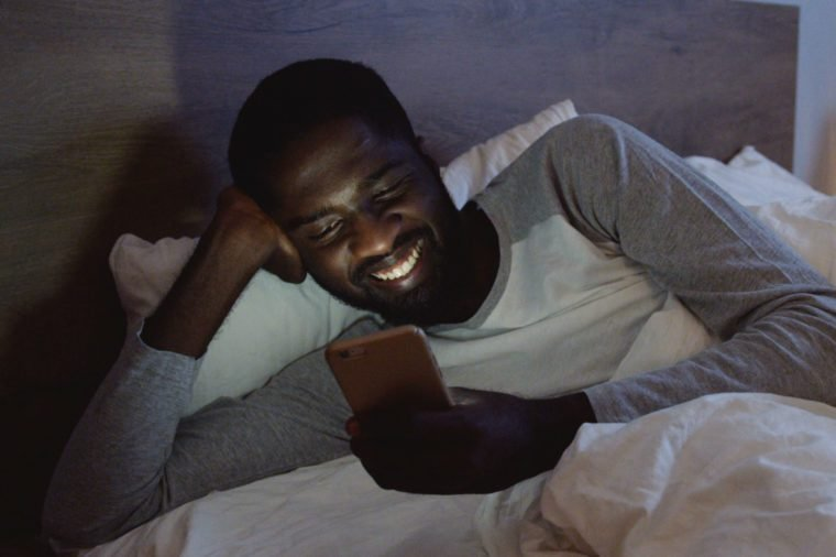 Young handsome African American man lying in the bed in his pajama and chatting with somebody cheerfully on the smartphone. At night.