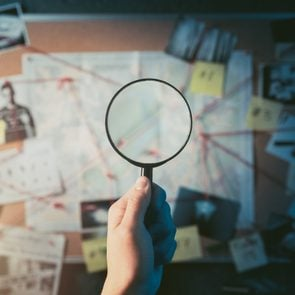Detective hand holding a magnifying glass in front of a board with evidence, crime scene photos and map. high contrast image
