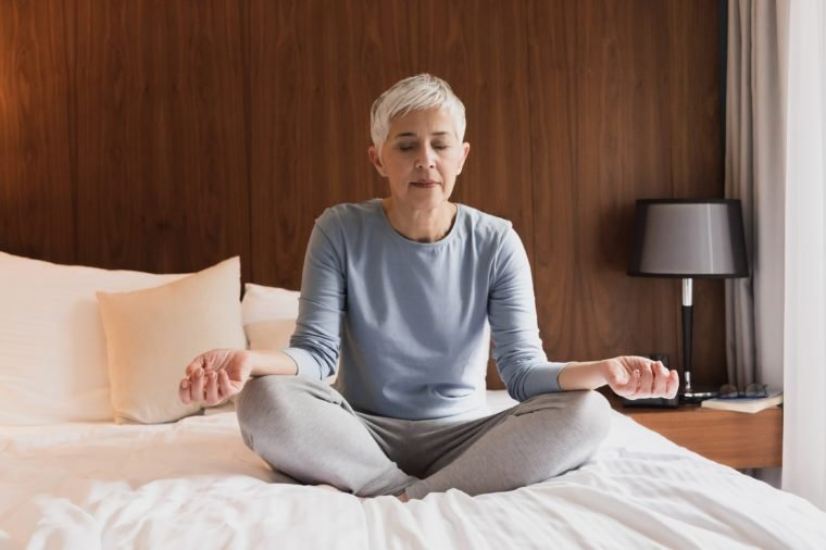 Beautiful senior woman doing yoga in her bedroom, Healthy morning routine and meditation concept