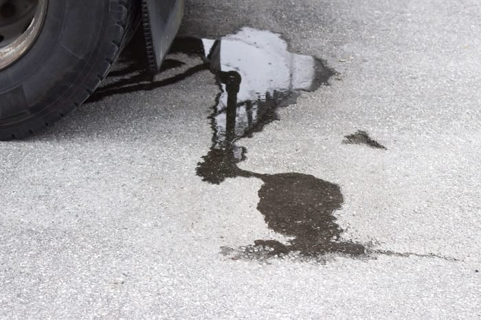Oil stain on the pavement under the car. Dirty asphalt under the car.
