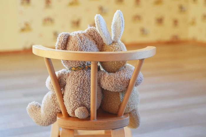 Best friends teddy bear and bunny plush toy sitting on wooden rocking horse or bench indoors hugging each other, back view with copy space. Love, family, childhood and friendship concept.