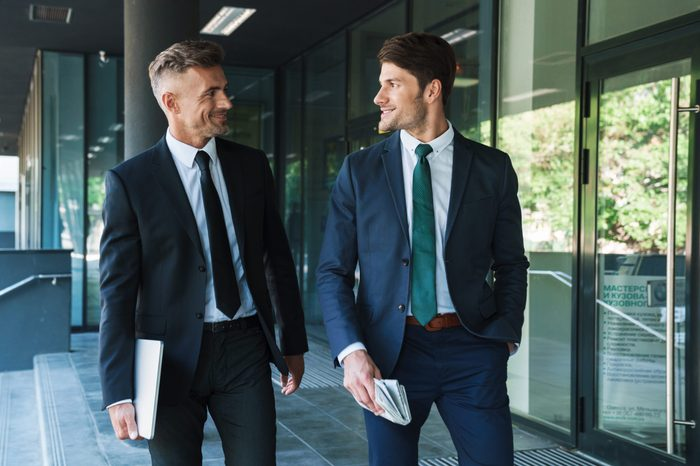 Portrait of two pleased businessmen partners dressed in formal suit walking and having conversation outside job center during working meeting