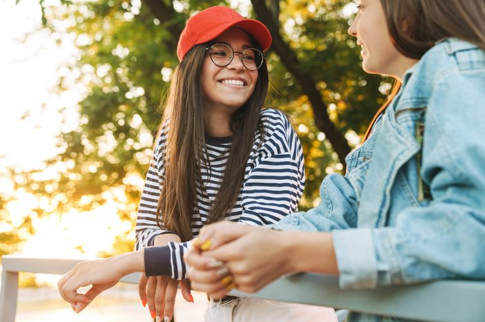 Image of two happy girls wearing eyeglasses smiling and talking while bending on railing in green park