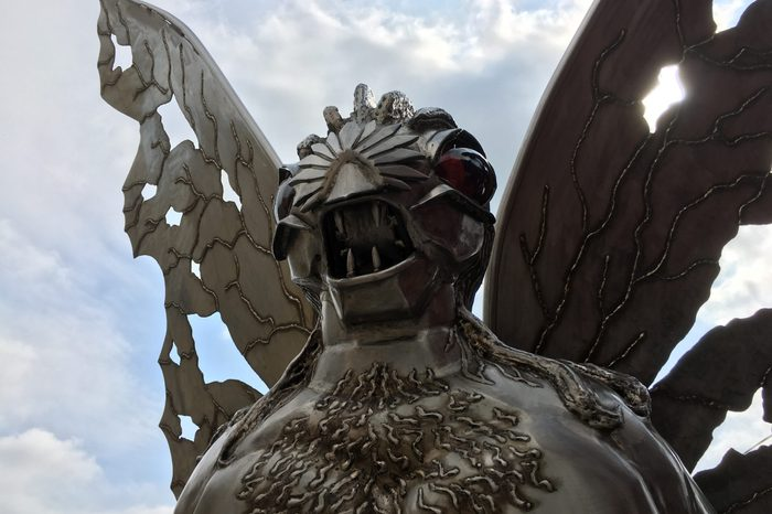 Point Pleasant, West Virginia / USA - September 2, 2019: Silver Mothman Statue Backlit on Cloudy Day