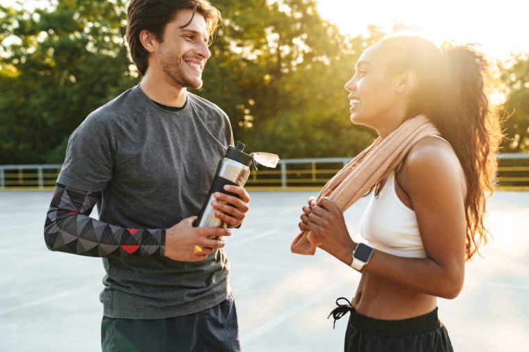 Image of a cheerful pleased young strong sports woman and man holding towel and water talking with each other outdoors.