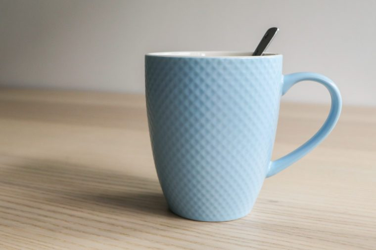 Blue mug with spoon on wooden table