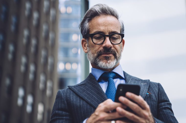 Low angle of elegant grey-haired mature male manager in expensive suit and glasses browsing smartphone on blurred background with New York skyscrapers