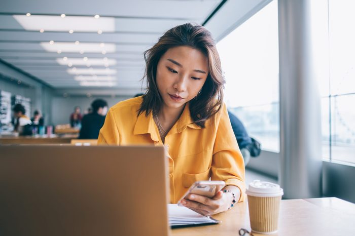 Beautiful focused Asian woman browsing smartphone in front of laptop in workspace in Hong Kong city with people in background