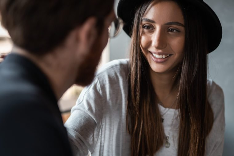 Cheerful young woman in hat smiling and talking with anonymous man during romantic date in cafe