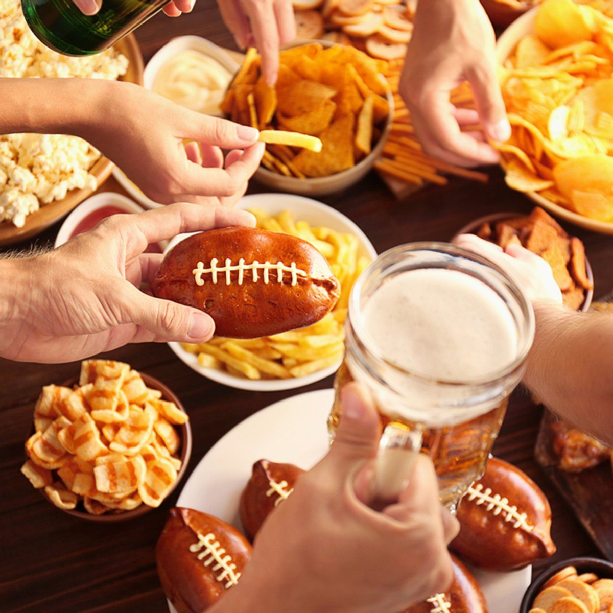 Close up view of hands taking snacks from plates during party; Shutterstock ID 552645409