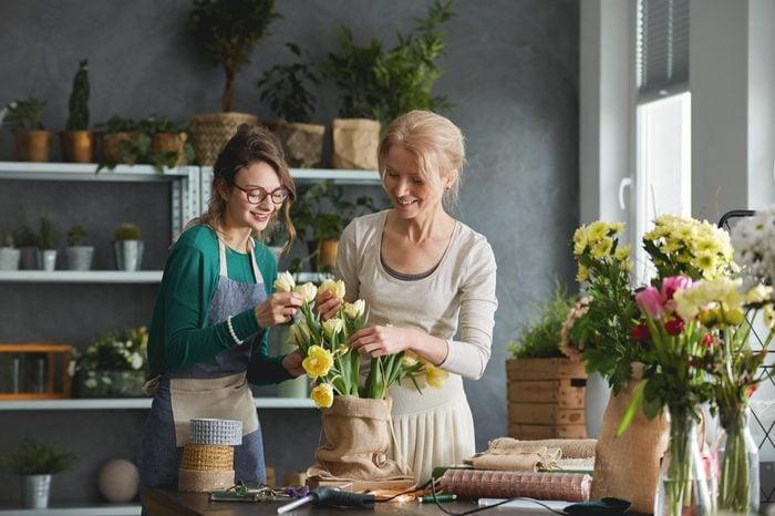 Creative florists preparing tulip bouquet in sack