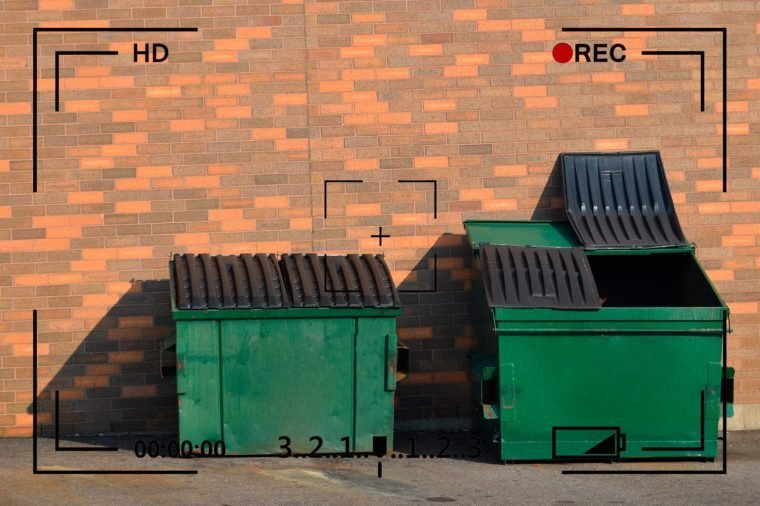 garbage dumpsters next to brick wall with camera info overlay