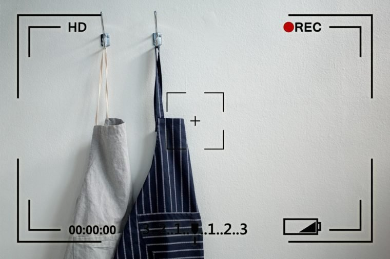 two aprons hanging on hooks on a white wall with camera info overlay