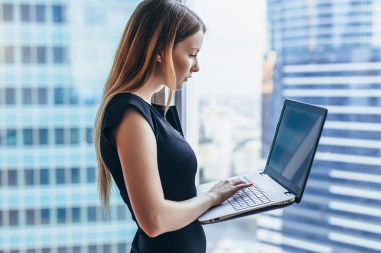 Portrait of young woman working holding laptop standing against panoramic window with city view