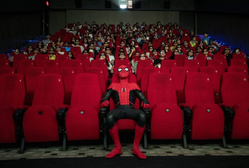 spiderman sits in the front row of a movie theater