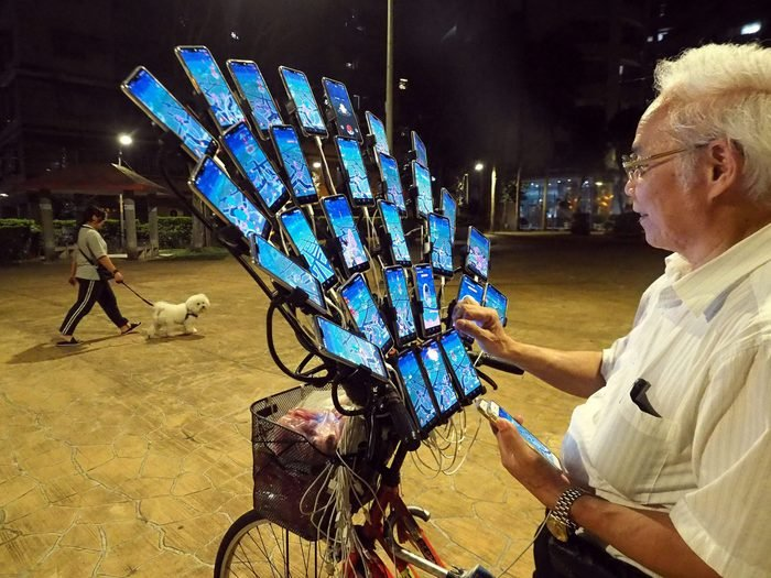 an old man with an array of 29 cellphones mounted on his bike plays pokemon go