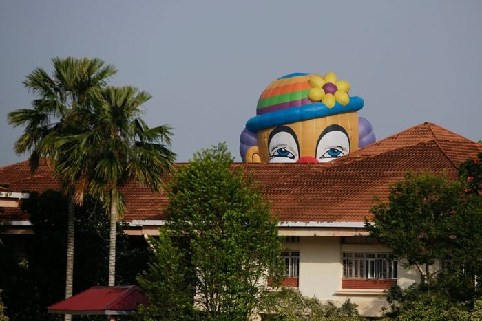 a clown face hot air balloon rises over a building