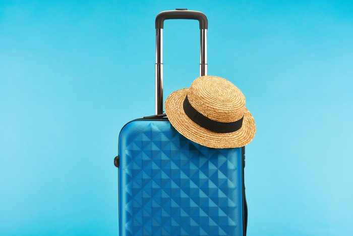 blue colorful travel bag with handle and straw hat isolated on blue