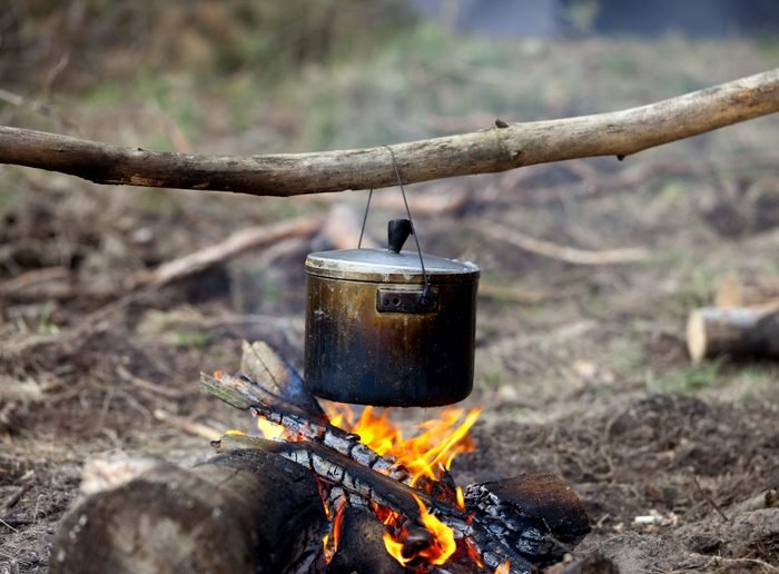 Cooking in sooty cauldron on campfire at forest