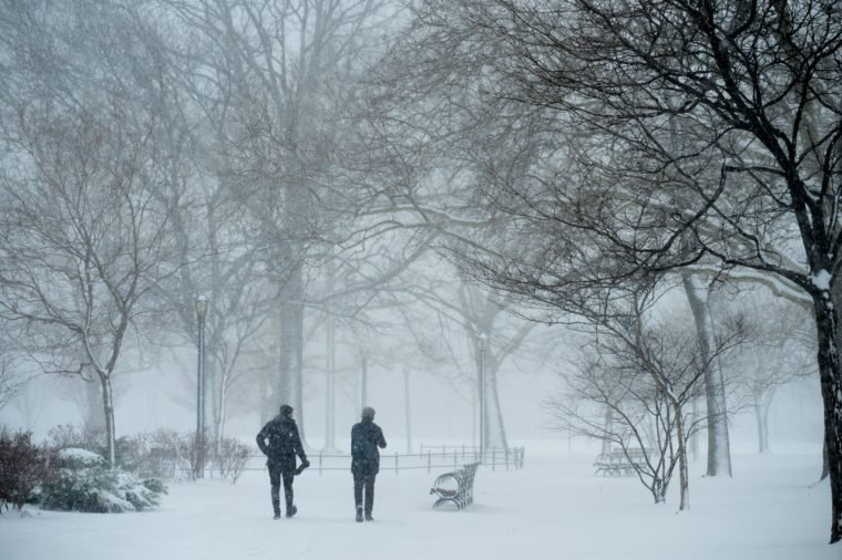 People walk through the streets of Brooklyn as a spring nor'easter