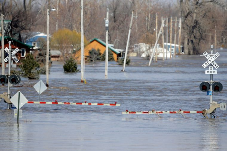 A railroad crossing is flooded with water