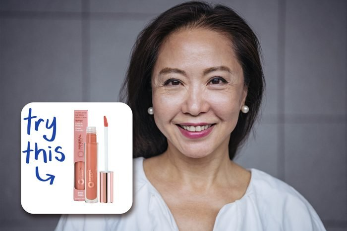 middle aged smiling woman with lipstick on, with lip gloss to buy
