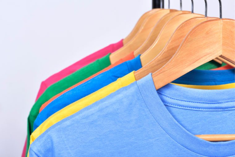 colorful tshirts hanging on a rack on wooden hangers