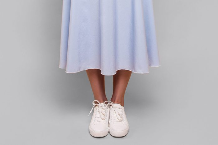 close up of long dress hem, ankles, and sneakers
