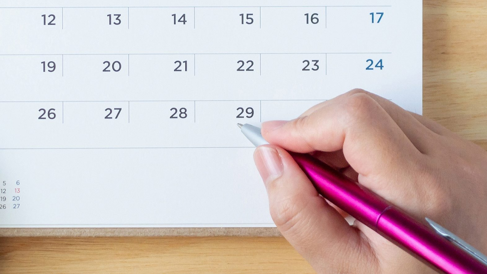 hand holding pen to a calendar on the table.