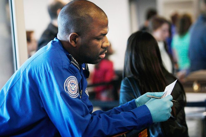 A Transportation Security Administration officer looks over the identification of a passenger during a security screening November 24, 2010 at LaGuardia airport in the Queens Borough of New York City