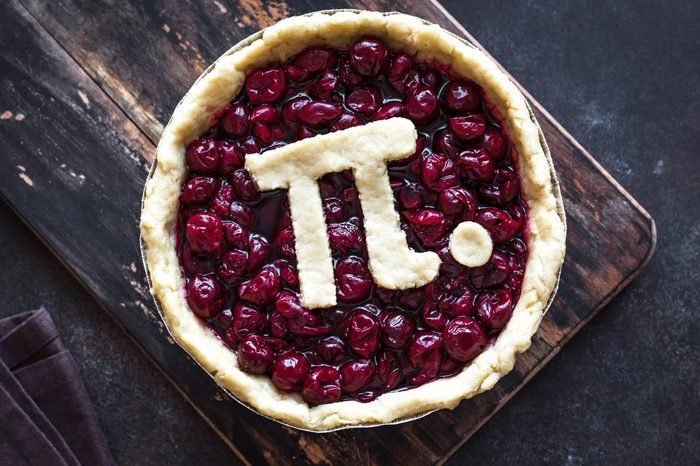 Pi Day Cherry Pie - making homemade traditional Cherry Pie with Pi sign for March 14th holiday, close up.