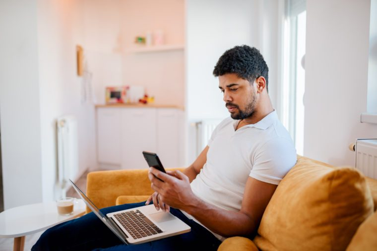 Young man sitting on sofa with laptop and mobile phone.