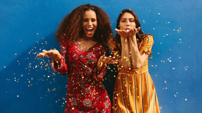 Female friends blowing glitter off their hands. Excited women having fun against blue wall.