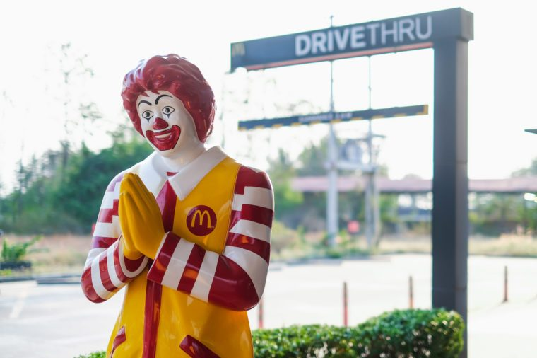 mcdonalds statue by a drive thru height clearance sign