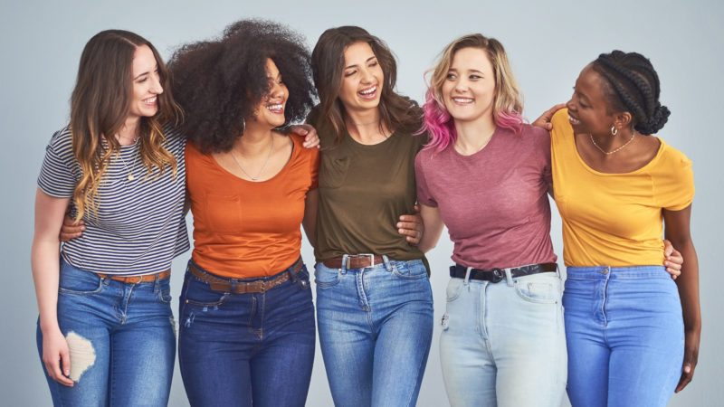 Studio shot of a group of diverse young women embracing against a gray background