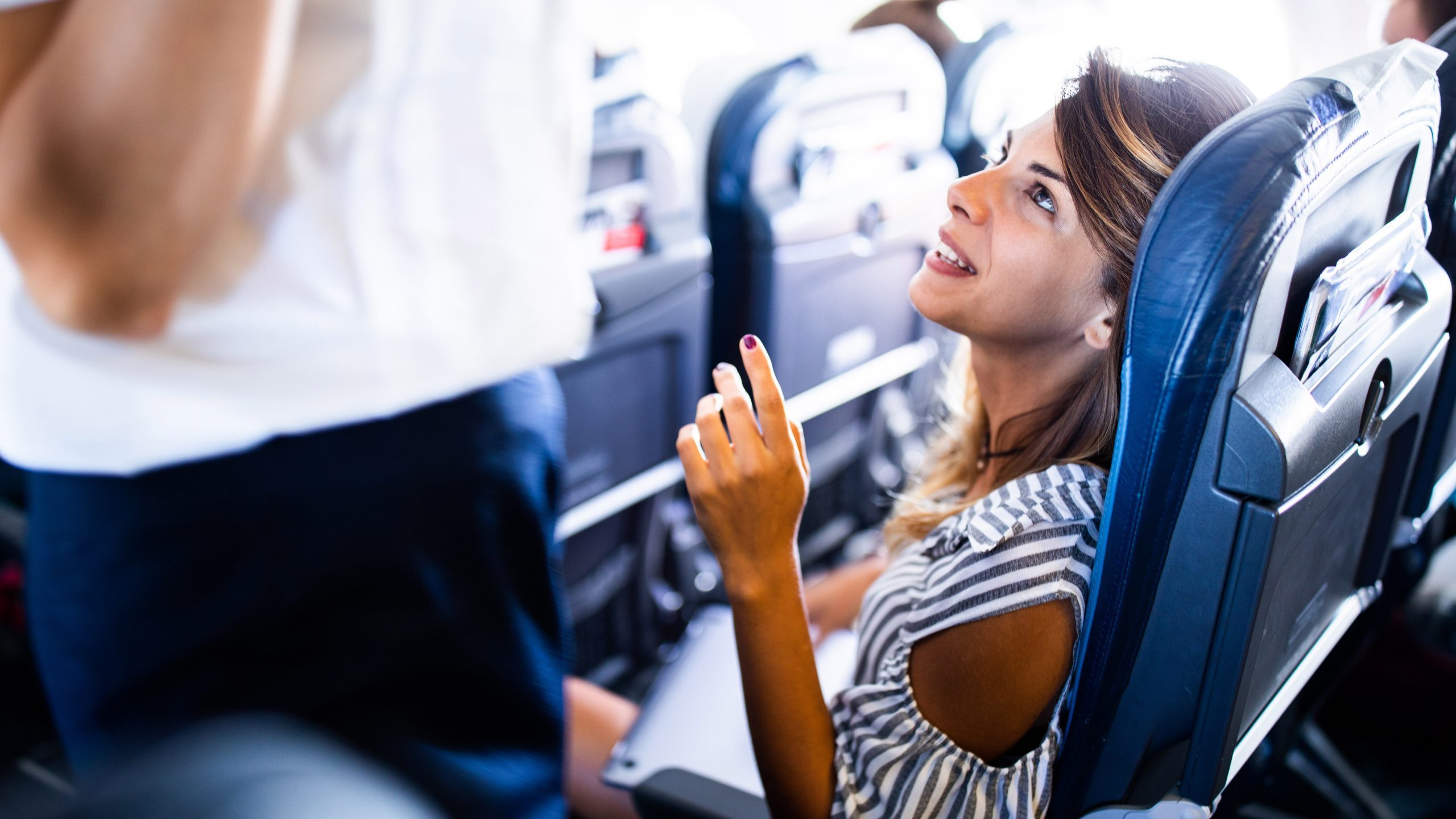 woman asking the flight attendant a question