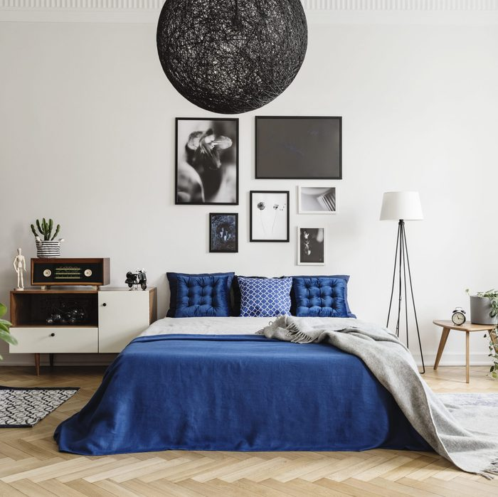 bed. bedroom. gallery wall. lamp and night stand.