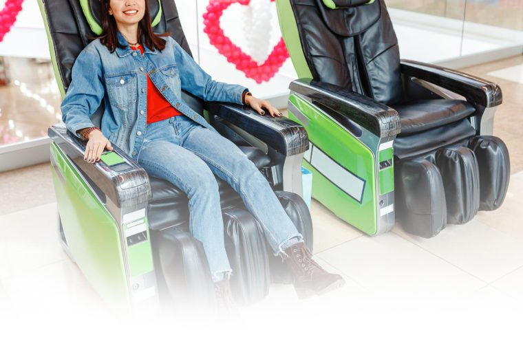 woman relaxing in a coin operated massage chair in an airport