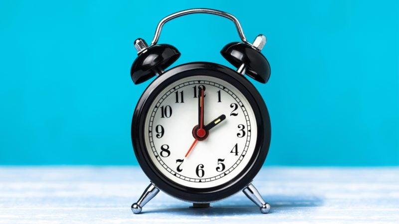 Retro black alarm clock on blue background. Alarm at 7 o'clock clock hand at 2 o'clock