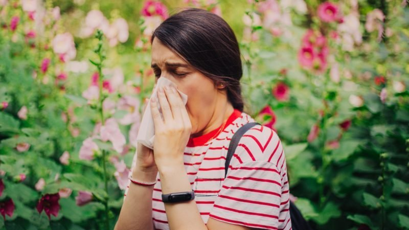 woman sneezing with a tissue outside. blurred flowers background.