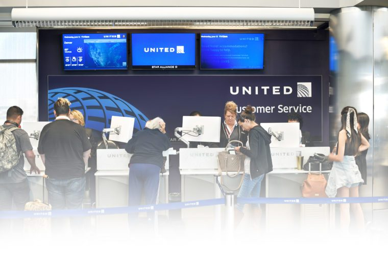 Passengers talk with United Airlines Customer Service agents at Denver International Airport in Denver, Colorado.