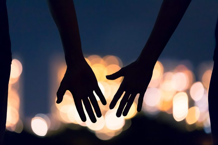 silhouette of two hands coming together or falling apart