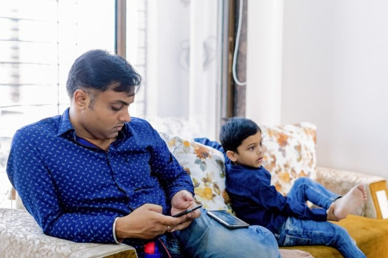 Father busy looking at his phone next to his son on the couch