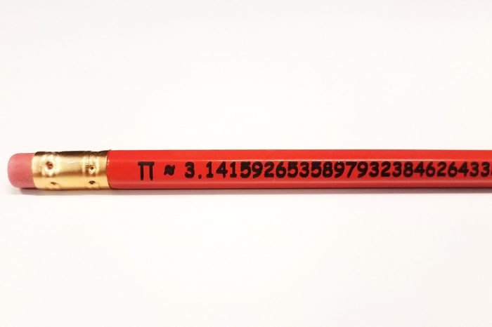 orange wood pencil with mathematical constant pi digits on white background