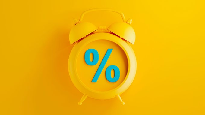yellow alarm clock on yellow background with blue percent symbol