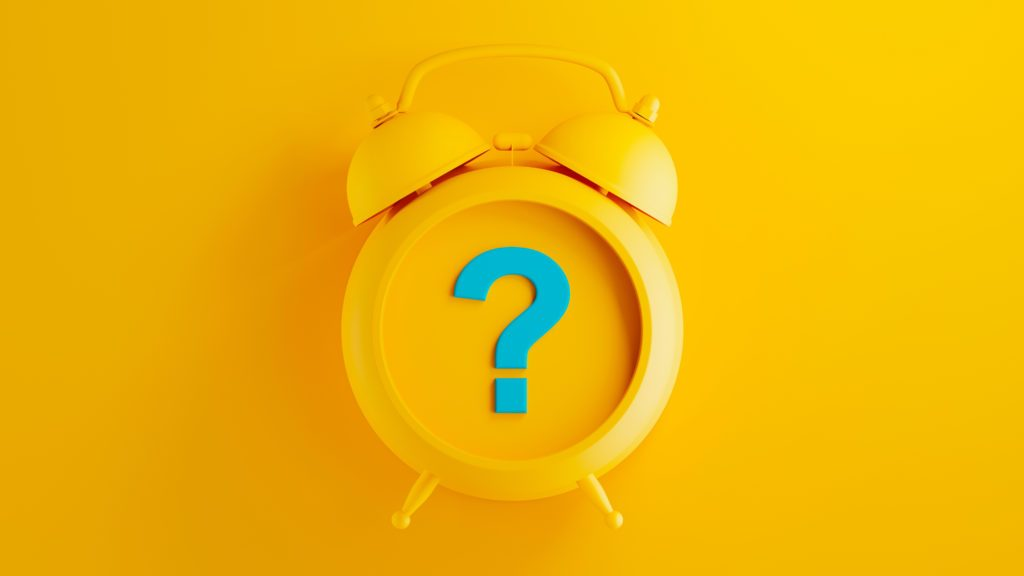 yellow alarm clock on yellow background with blue question mark symbol