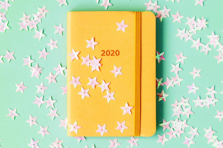 star confetti on yellow notebook on teal background