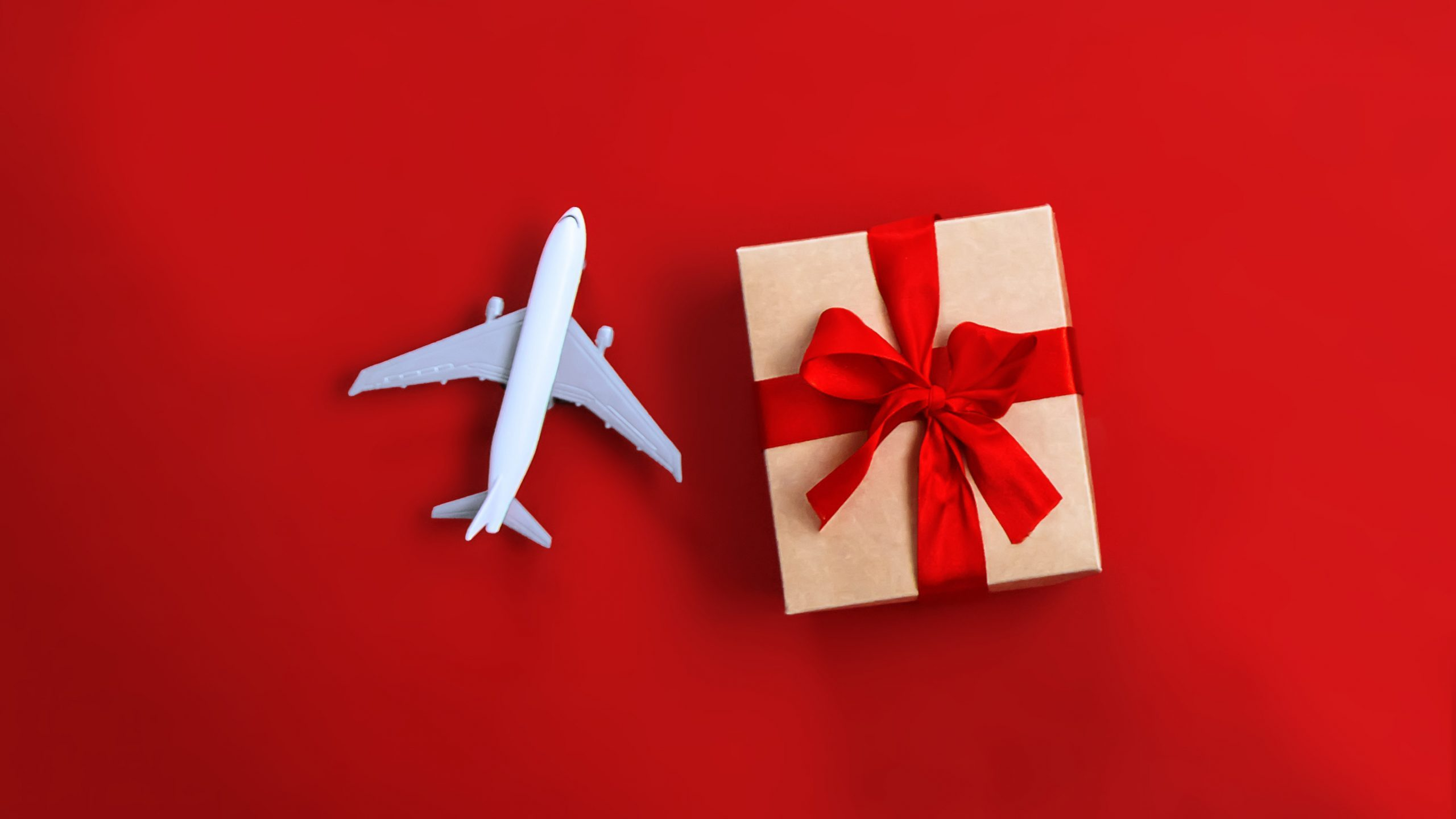 toy plane and gift on red background
