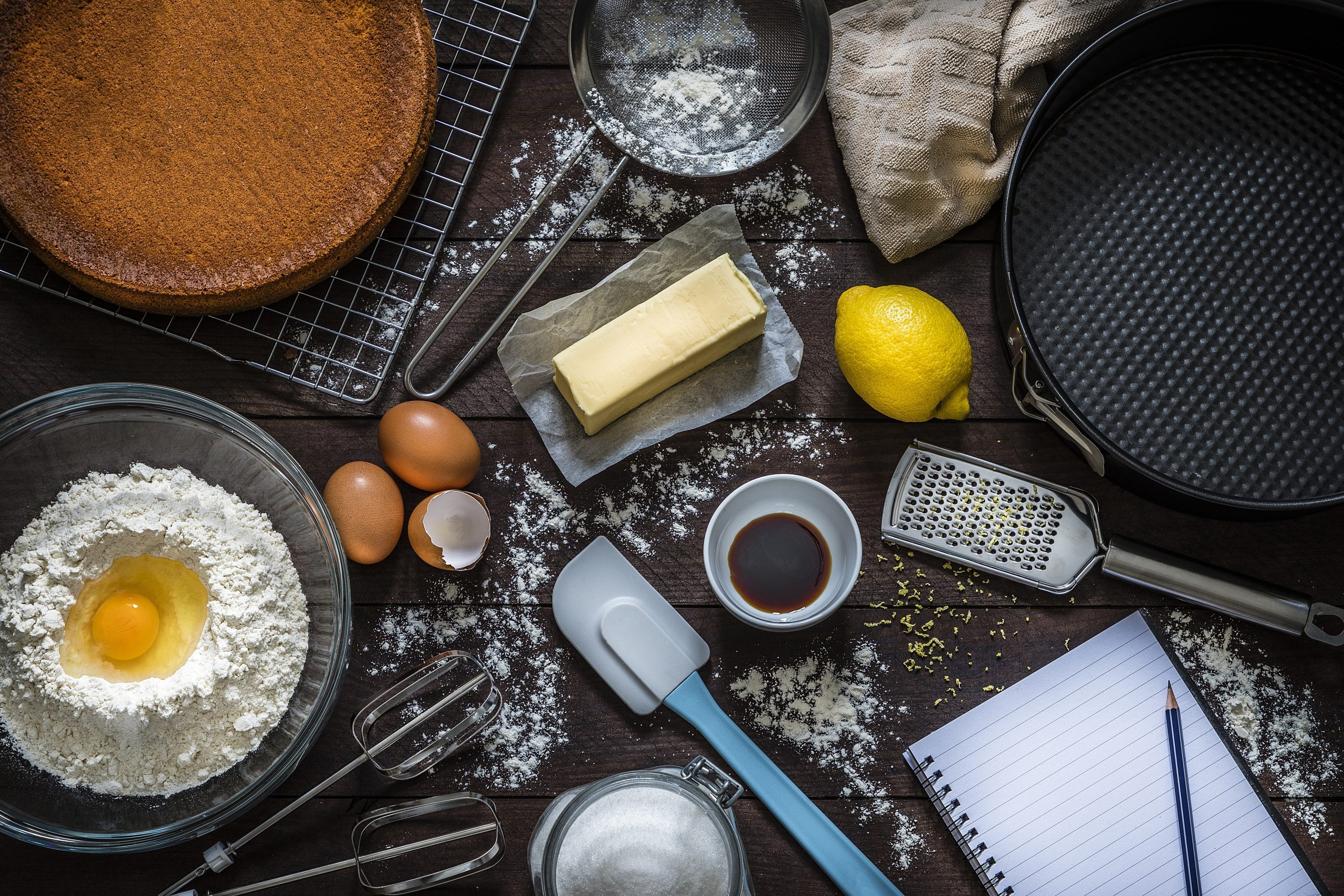 Top view of various ingredients and utensils for baking cakes or cooking desserts like flour, eggs, sugar, butter, a spatula, a sieve, a baking mold and a grater with lemon zest. At the lower right corner is an opened cookbook with copy space ideal for a text, a logo or a recipe. All the objects are on a rustic wooden table. Low key DSLR photo taken with Canon EOS 6D Mark II and Canon EF 24-105 mm f/4L